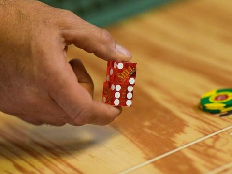 Hand rolling dice at a table game of craps.